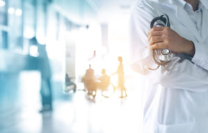 doctor holding stethoscope with blurred hospital hallway in background
