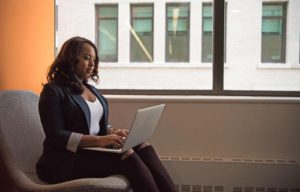 woman in business attire holding laptop